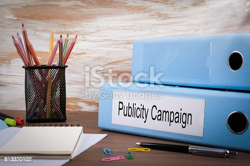 842214626istockphoto Publicity Campaign, Office Binder on Wooden Desk. On the table colored pencils, pen, notebook paper 813320102