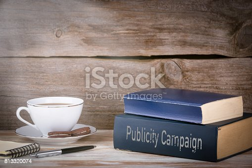 842214626istockphoto Publicity Campaign. Stack of books on wooden desk 813320074