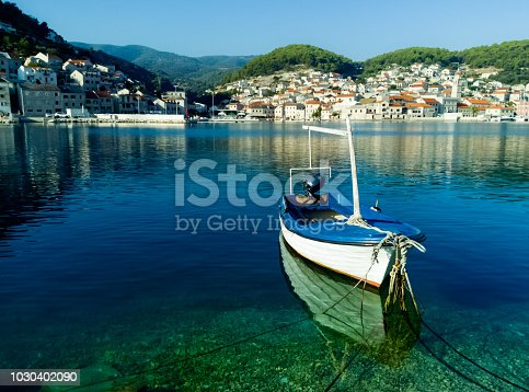 Small boat moored in the port of the town of Pucisca, on the island of Brac, Croatia, Dalmatia. Crystal clear blue water, a boat and its reflection in the water, and in the background a small town Pucisca. A summer morning. Summer travel destination.