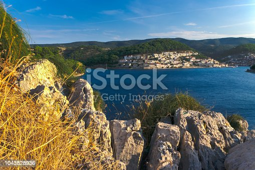 View of the bay and the coastal town of Pucisca on the island of Brac, in Dalmatia, Croatia. Calm blue sea and blue sky. Late afternoon - golden hour. Summer travel destination. HDR photo.