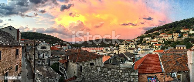 Colorful sunset over Pucisca on Brac island, Croatia. This beautiful place arose from stone in a deep cove on the north of Brač. Nicely built stone houses with paved white roofs give the place its charm. Pučišća has always been known for its culture of stone masonry.