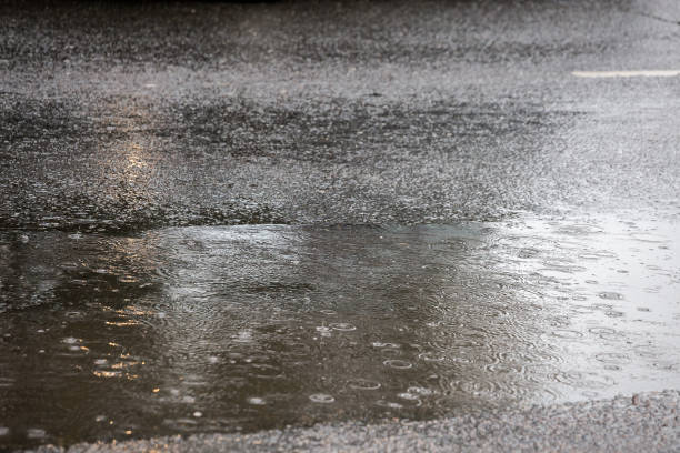 puddle on asphalt road at rain in city with selective focus and boke blur stock photo