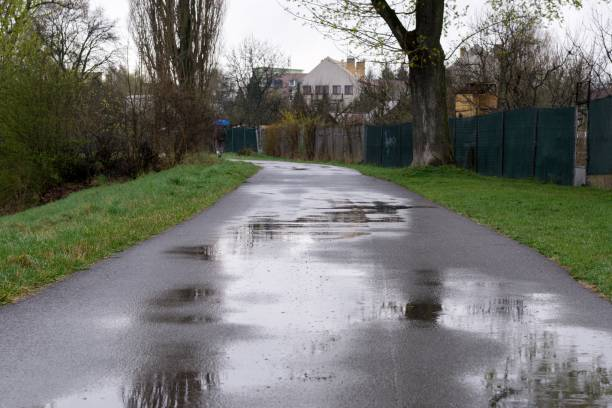 puddle on road during rain. - wet stock pictures, royalty-free photos & images