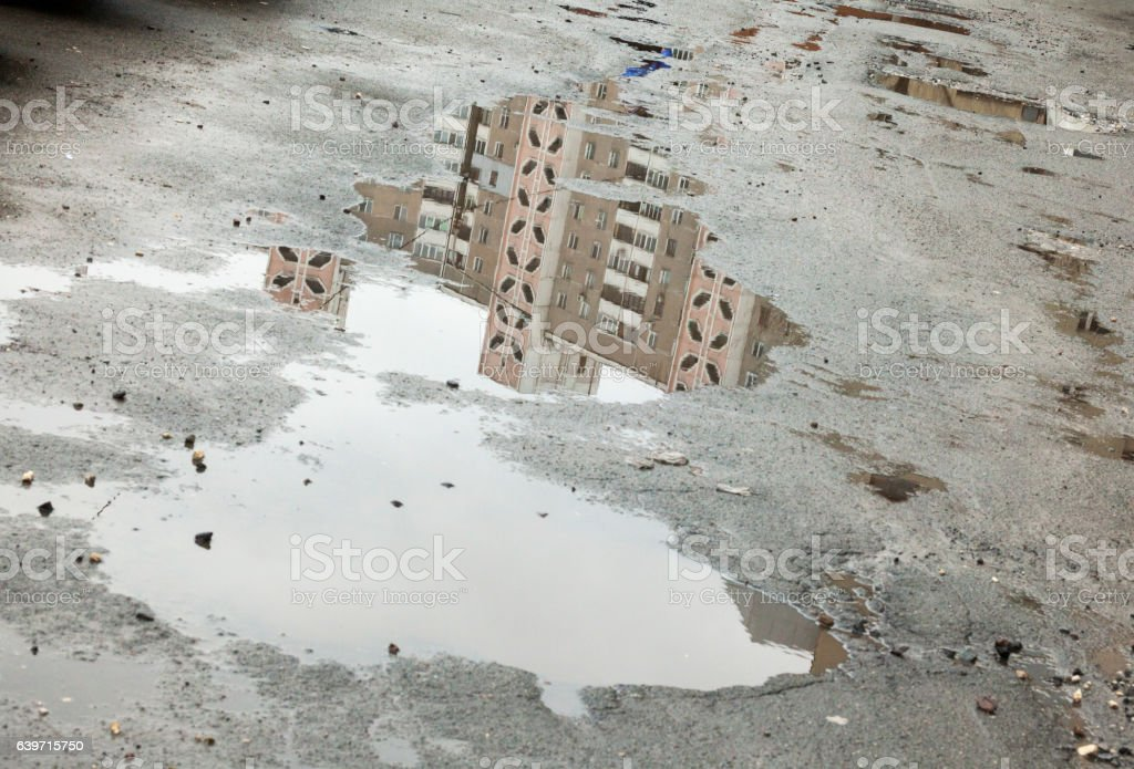 Puddles in the potholes of the old asphalt. stock photo