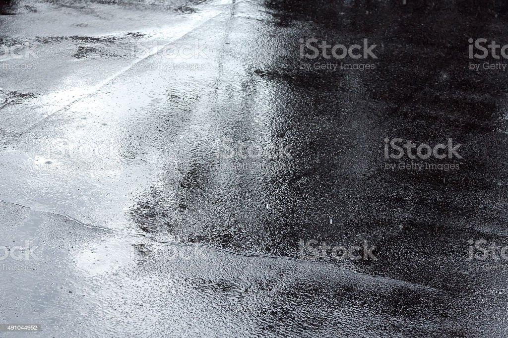 puddles of water on a pavement after rain stock photo