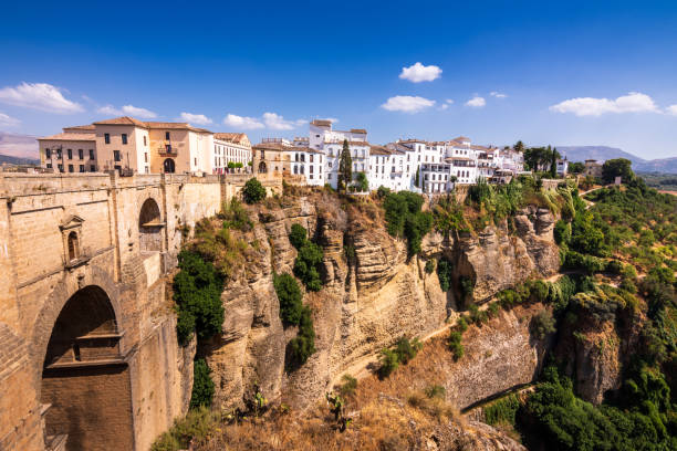 Puente Nuevo stone bridge and Pueblos Blancos on edge of El Tajo Gorge in mountaintop town of Ronda in Spain stock photo