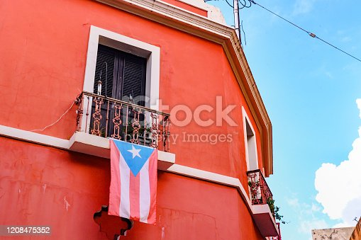 This is a color photograph of a Puerto Rican flag hanging from the balcony of a red building in Old San Juan, Puerto Rico, USA.