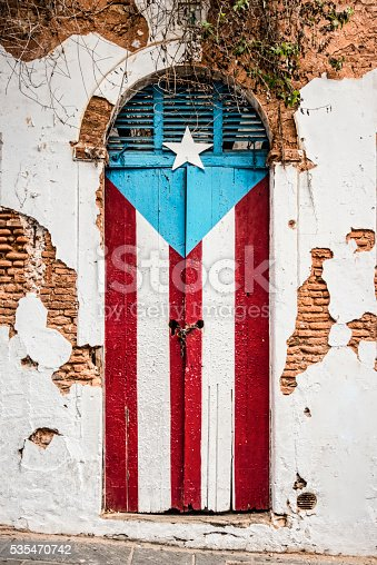 Puerto Rican flag painted on the door of an old abandoned building. San Juan, Puerto Rico.