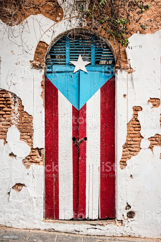 Puerto Rican flag on abandoned building door. stock photo