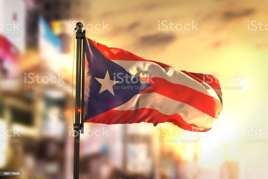 Bandeira de Porto Rico contra cidade turva fundo no Sunrise Backlight - foto de acervo