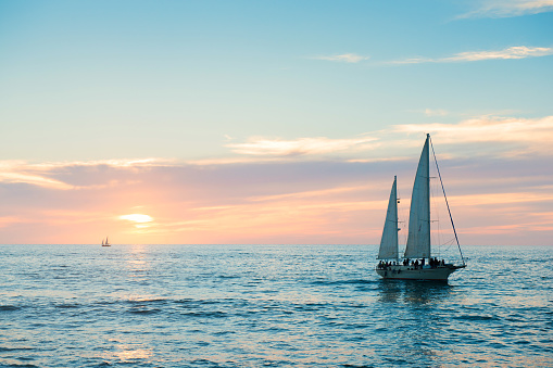 This is a horizontal, color photograph shot in travel destination, Puerto Vallarta, Mexico. A sailboat moves through the Pacific Ocean at sunset as it drives back toward the docks.