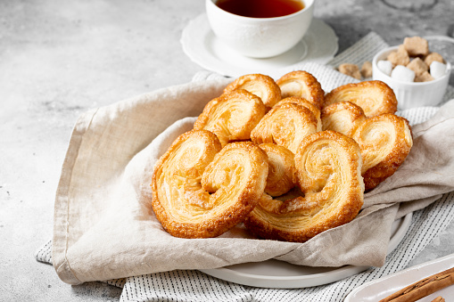 Puff. Flaky sugar Palmiers cookies in a ceramic plate on a light background. Sweet homemade cakes