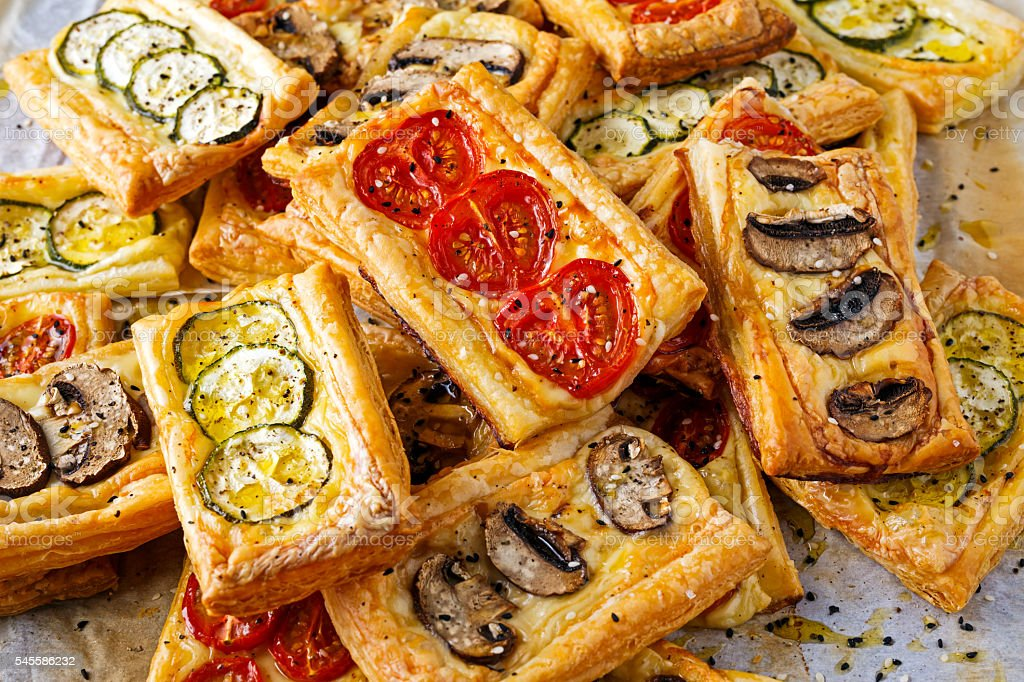 Puff pastry appetizers with vegetables, mushrooms, tomatoes, zucchini and cheese. stock photo