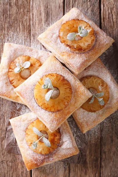 blätterteig-kuchen mit ananas, dekoriert mit minze und puderzucker nahaufnahme. vertikale ansicht von oben - ananaskuchen stock-fotos und bilder