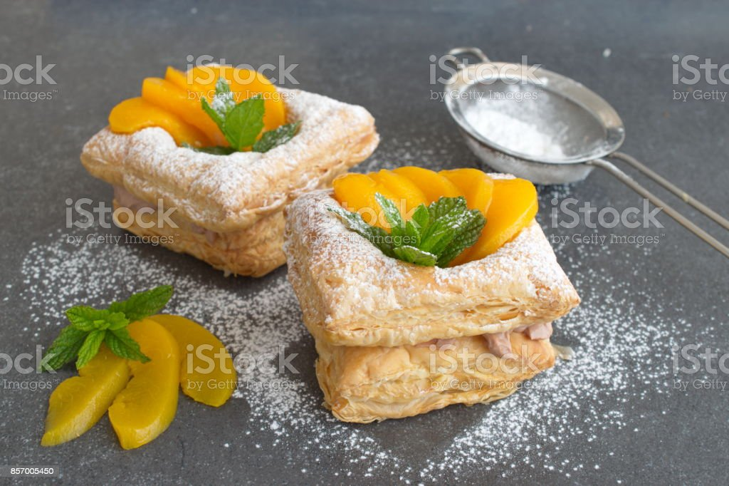 Puff pastry cookies with chokolade cream and tinned apricotes stock photo