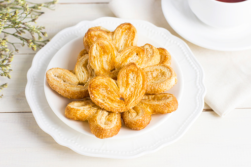 Puff pastry hearts on a white plate with a Cup of tea