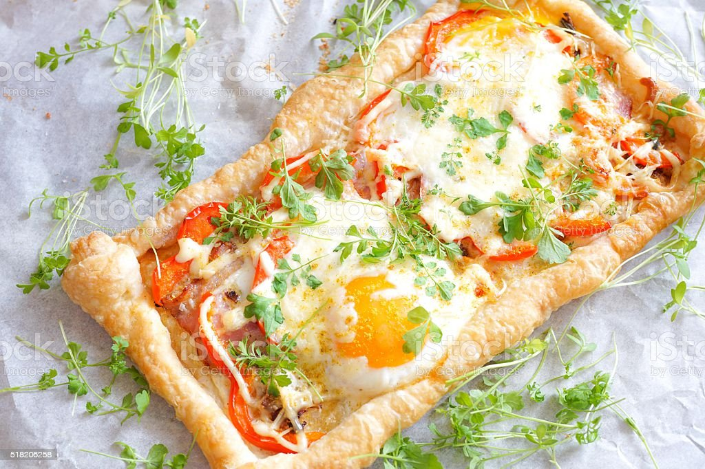Puff pastry tart with egg and bacon stock photo