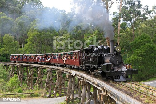 Belgrave, Australia - March 14, 2012: Puffing Billy heritage steam train crosses the famous Monbulk Creek wooden trestle bridge with a trainload of passengers enjoying the ride and spectacular forest views.  For more than a century, the steam train has operated on the original 2'6