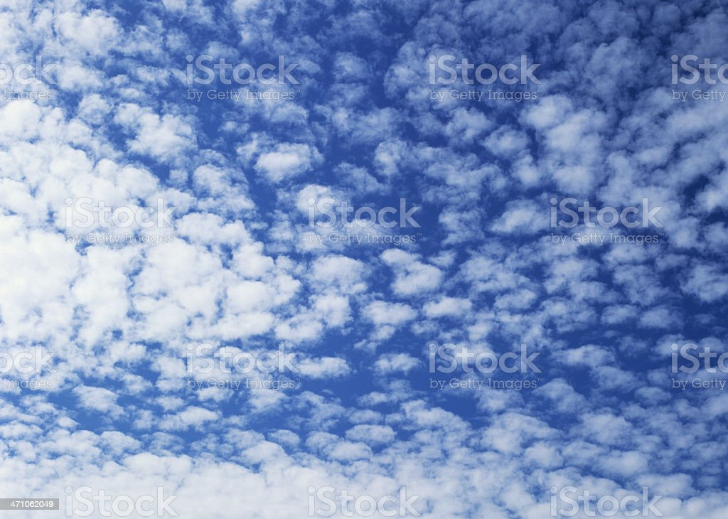 Puffy white clouds against bright blue sky stock photo