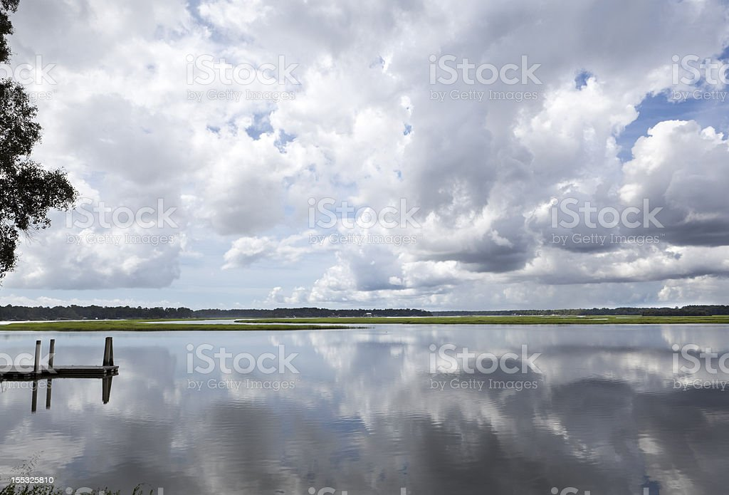 Puffy White Clouds Dock Reflected Smooth May River Bluffton SC stock photo