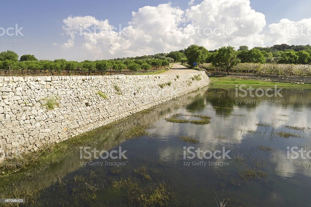 Puglia landscape,with pond and stone wall. royalty-free stock photo