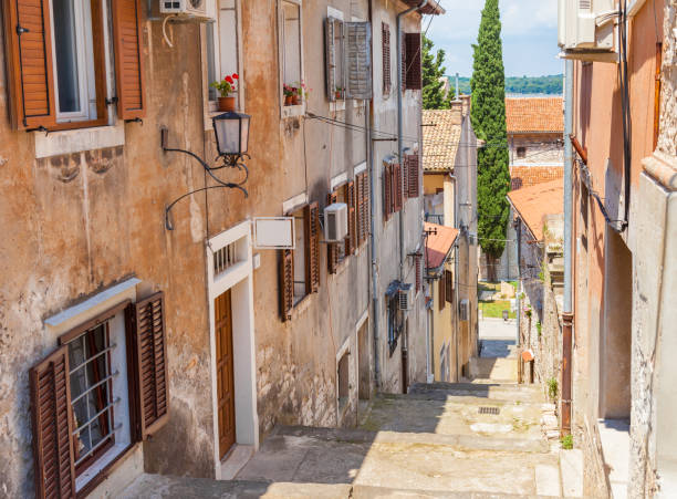 Pula, Croatia and old narrow street Narrow street with stairs down and typical houses in old town of Pula city in Croatia. croatian culture stock pictures, royalty-free photos & images