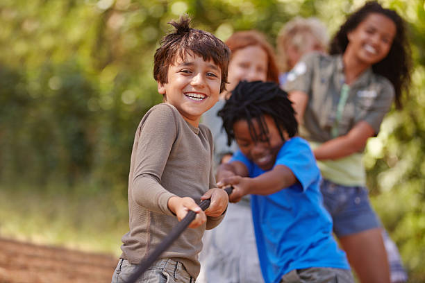 Pull! A group of kids in a tug-of-war game pre adolescent child stock pictures, royalty-free photos & images