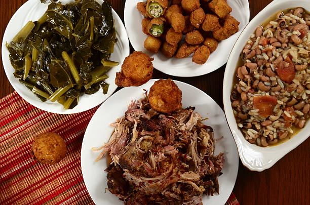 Pulled Pork Barbecue Dinner Barbecued pulled pork with collard greens, hush puppies, fried okra, and hoppin' john, a dish often eaten on New Year's Day for good luck. southern usa stock pictures, royalty-free photos & images