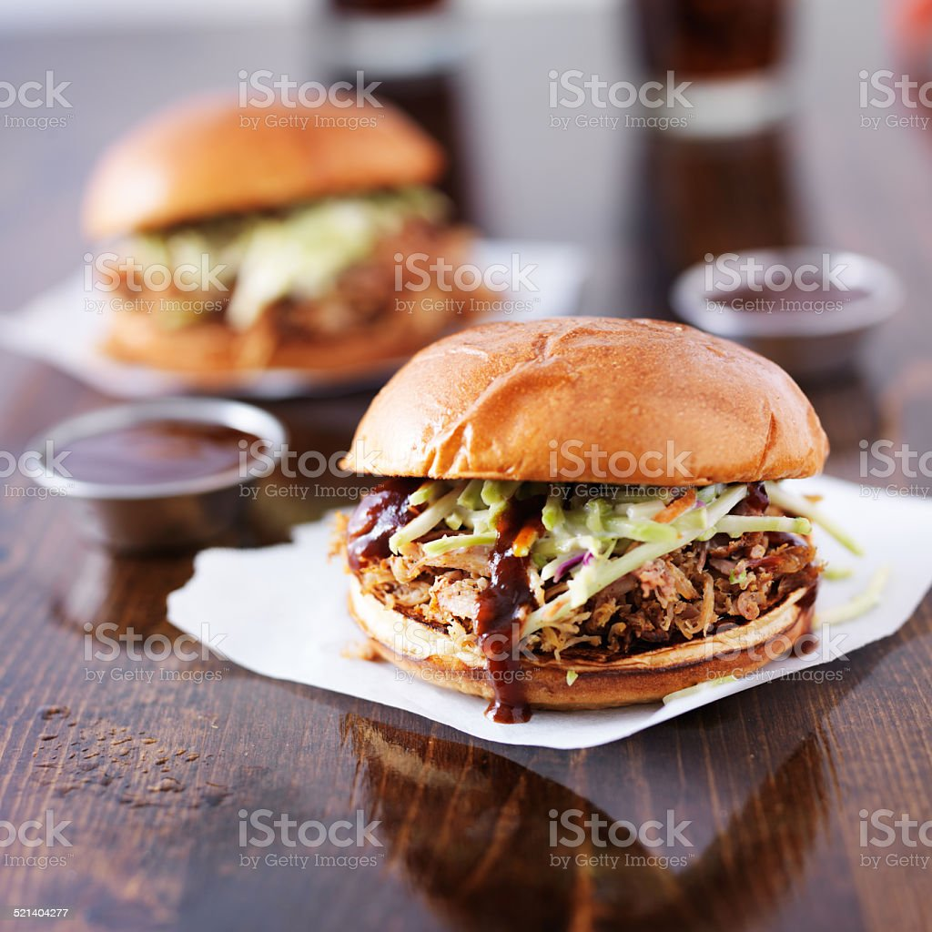 pulled pork barbecue sandwiches with condiment cups stock photo