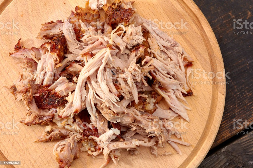 Pulled pork on round wooden board stock photo