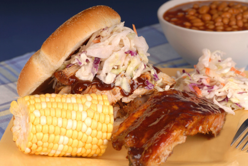 Pulled pork sandwich with slab of ribs, ear of corn, cole slaw and beans