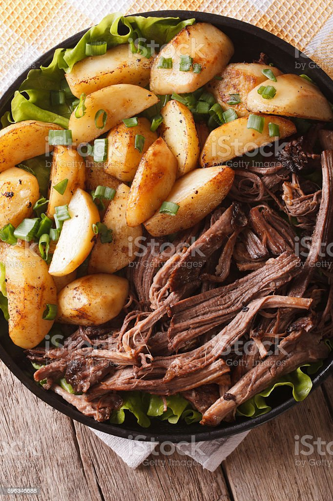 Pulled pork with baked potatoes close-up on a plate. vertical royalty-free stock photo