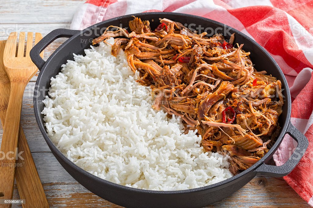 pulled  pork with long-grain basmati rice in iron stewpot stock photo