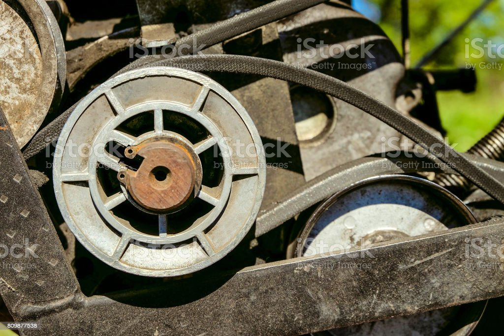 Pulley with belt drive of agricultural motorized machine. Agrimotor detail. stock photo