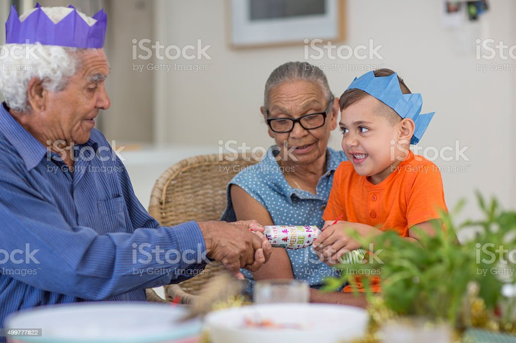 Pulling a christmas cracker with Grandad stock photo