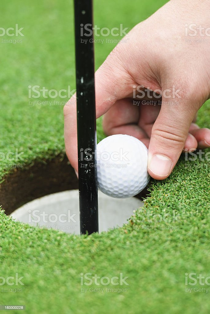 pulling out the golf ball royalty-free stock photo