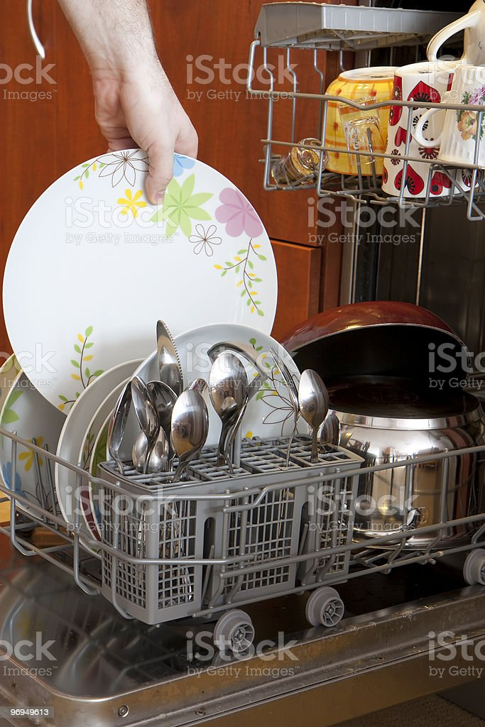 Pulling plate out of dishwasher royalty-free stock photo