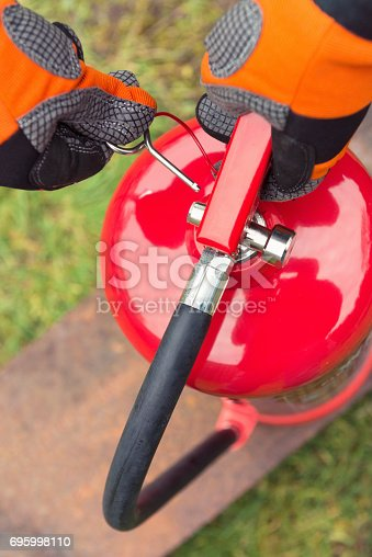 Close-up on a man's hands, as he pulls out the safety pin, in preparation for using a fire extinguisher.