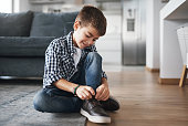 Shot of an adorable little boy tying his shoelaces at home