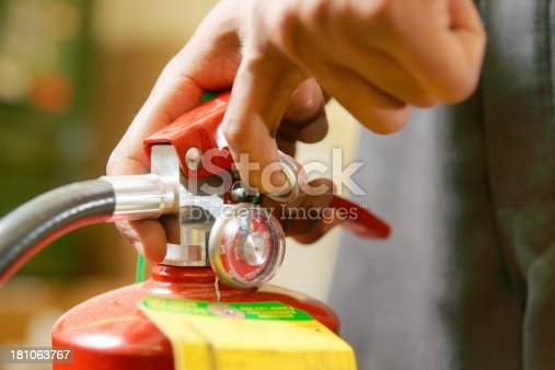 A close-up of pulling the safety pin on a fire extinguisher