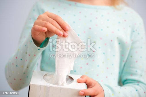 Young girl pulling a tissue out of a box. See also:
