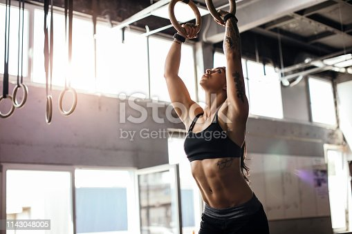 Fitness athlete working on arms and abs using gymnastic rings