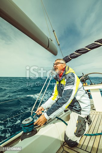 Man pulling winch rope on sailing boat