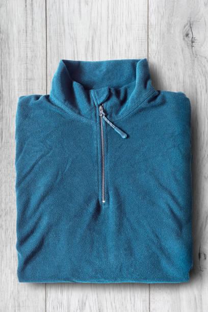 pullover auf holzhintergrund - fleecepullover stock-fotos und bilder