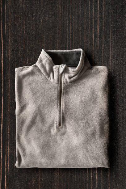 pullover auf hölzernen hintergrund - fleecepullover stock-fotos und bilder