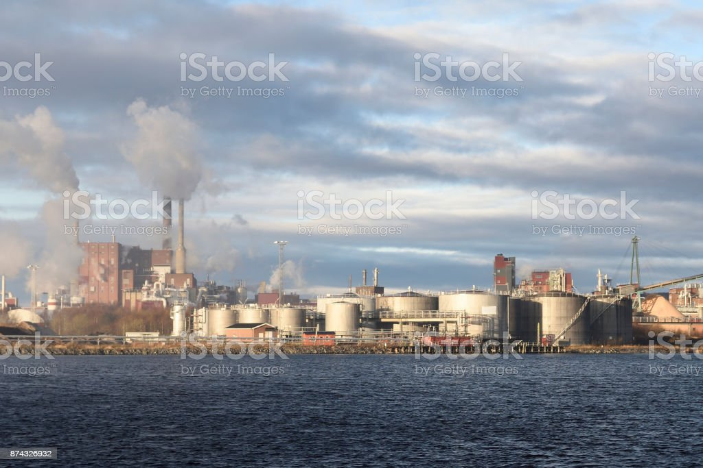 Pulp factory with lot of smoke comming out of chimneys stock photo