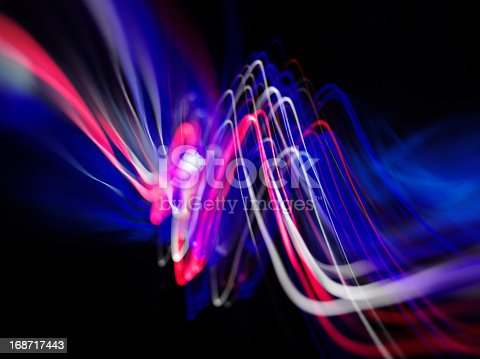 Waves of coloured lights with copy space on a dark background.