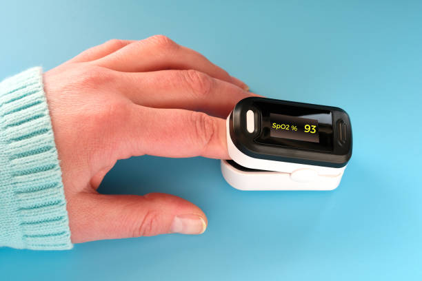Pulse Oximeter portable digital device to measure person's oxygen saturation. Reduction in oxygenation is an emergency sign of Covid-19 viral pneumonia requiring immediate hospitalization. Pulse Oximeter, finger digital device to measure oxygen saturation in blood. Reduced oxygenation is an emergency sign of pneumonia, for instance caused by coronavirus. Device on Caucasian female hand. saturated color stock pictures, royalty-free photos & images