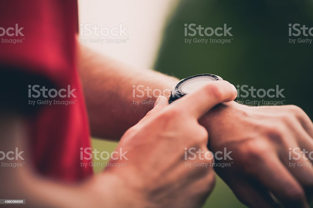 Pulse trace, runner check heart rate on smart watch stock photo