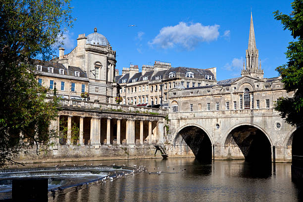Pulteney Bridge and the River Avon Pulteney Bridge and the River Avon in Bath.  St Michael's Church can be seen in the background. bath england stock pictures, royalty-free photos & images